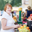 Stock Photo: Mature woman chooses fruits