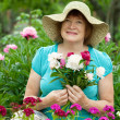 Happy mature woman with flowers — Stock Photo