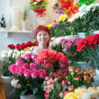 Stock Photo: Womin her small flower shop