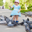 Two-year girl feeding doves — Stock Photo