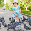 Happy two-year girl playing with doves — Stock Photo