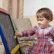 Child draws on blackboard with chalk — Stock Photo