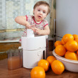 Baby girl making fresh orange juice — Stock Photo #12517335