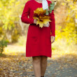 Happy mature woman with maple posy - Stock Photo