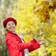 Happy mature woman throwing  maple leaves - Stock Photo