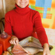 Woman is cooking fish - Stock Photo