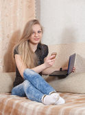 Girl speaks by mobile and uses laptop — Stock Photo