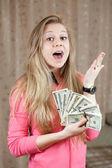 Happy woman shows bundles of US dollars — Stock Photo