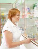 Woman near counter in pharmacy — Stock Photo