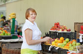 Woman chooses fruits at market — Stockfoto