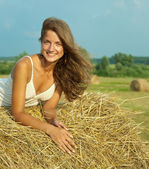 Girl laying on straw bail — Stock Photo
