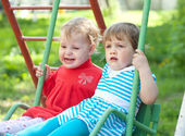 Two children on swings — Stock Photo