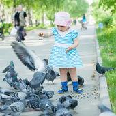 Dva rok dívka krmení holubů — Stock fotografie