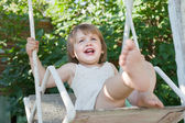 Laughing girl on swing in summer — Stock Photo