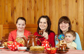 Women with child drinks tea and eats pancakes — Stock Photo