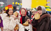 Women eating pancakes during Maslenitsa — Stock Photo
