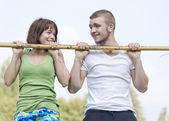 Loving couple hanging on the crossbar — Foto Stock