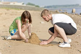 Family making a sand castle — Stock Photo