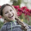 Beautiful girl laughs against tulips — Stock Photo #11233556