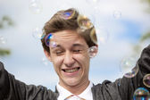 Portrait of the teenager in soap bubbles — Stock Photo