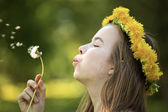 Beautiful girl blowing dandelion — Stock Photo