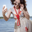 The girl in sun glasses looks at phone — Stock Photo