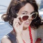 The lovely girl looks over sun glasses — Stock Photo