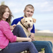 Happy couple with dog at the park — Stock Photo