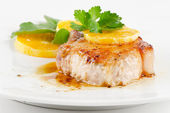 Fried pork steak with orange slice — Stock Photo