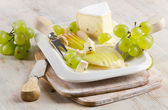 Cheese and grapes on wooden platter — Stock Photo