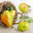 Fresh pears in the basket on a wooden table — Stock Photo