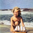 Girl with a model sailboat on the beach — Stock Photo