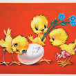 Three chick with flowers waiting for the fourth chick from an eg - Stock Photo
