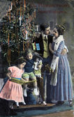 RUSSIA - CIRCA 1913: Postcard printed in Russia shows family near Christmas tree, circa 1913 — Stock Photo