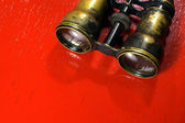 Vintage binoculars isolated on red background — Stock Photo