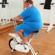 Overweight woman exercising on bike — Stock Photo #11081218