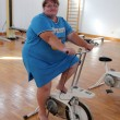 Overweight woman exercising on bike — Stock Photo #11081220