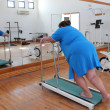 Overweight woman running on trainer treadmill — Stock Photo