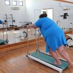 Overweight woman running on trainer treadmill — Stock Photo #11081221