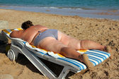Overweight woman sunbathe on beach — Stock Photo