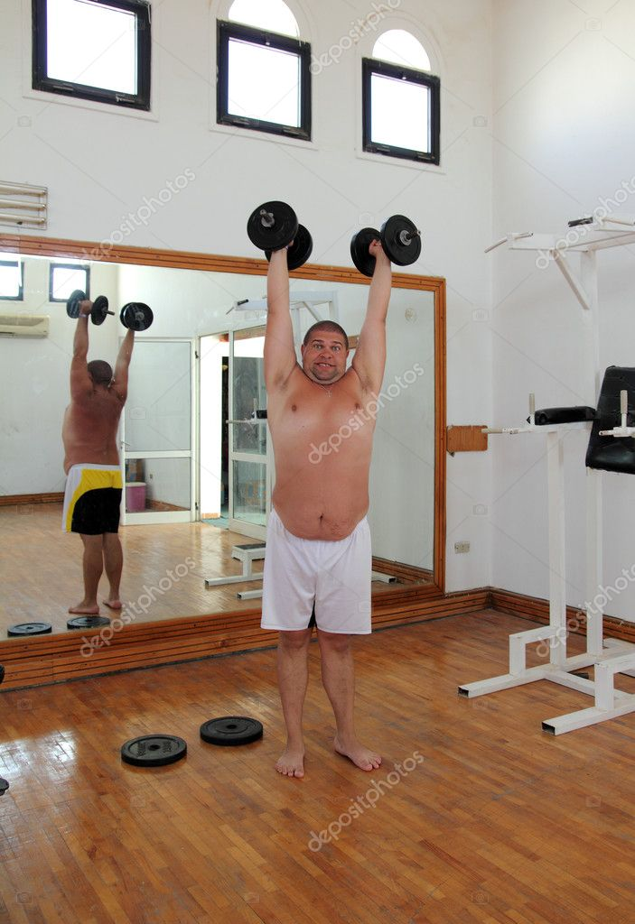 Fun overweight man with dumbbells in gymnasium — Stock Photo #11081533