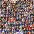 Blurred crowd of spectators on a stadium tribune - Stock Photo