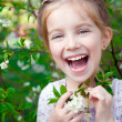 Little girl with bush blossoming tree - Stock Photo