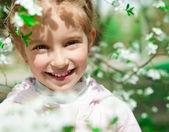 Niña con arbusto floreciente — Foto de Stock