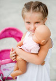 Little girl with toy carriage — Stock Photo