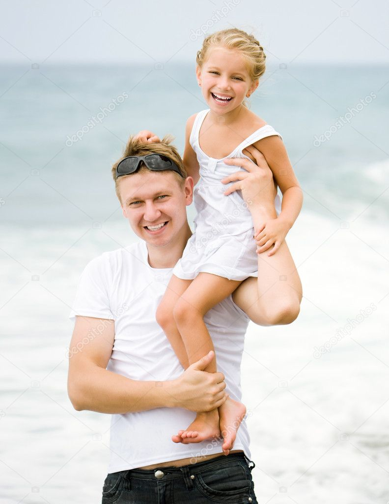 Happy father holding little daughter on his shoulder  Stock Photo #12095524