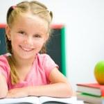 Little girl at the desk raised her hand — Stock Photo