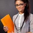 Beautiful student girl is holding an orange book — Stok fotoğraf