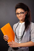 Beautiful student girl is holding an orange book — Stock Photo