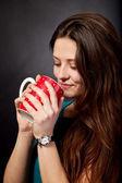 Güzel genç kız kırmızı bardağı götürüyor — Stok fotoğraf